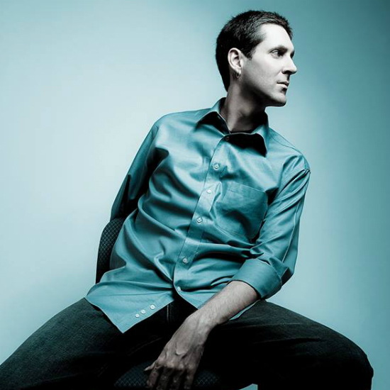 Nicolay+sitting+on+a+stool+wearing+a+satin+teal+shirt+that+matches+the+backdrop.jpg